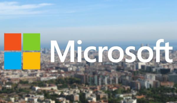 Fotomuntatge amb el logotip de Microsoft sobre una panoràmica de la ciutat de Barcelona, concretament bona part del districte tecnològic 22@